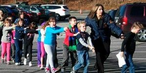 Police officer leading children to safety in Newtown, Connecticut
